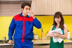 The woman with contractor at kitchen discussing repair Stock Image