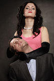 Woman in control of man. Female controls her guy. Studio shot on black grey background stock photos