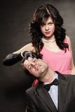 Woman in control of man. Female controls her guy. Studio shot on black grey background stock photo