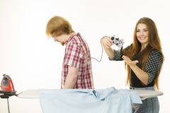 Woman controling man to do ironing. Woman being bossy having fun while steering men using gaming pad. Female controling her boyfriend to do ironing. Household Royalty Free Stock Image
