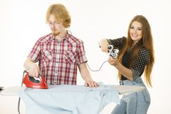 Woman controling man to do ironing. Woman being bossy having fun while steering men using gaming pad. Female controling her boyfriend to do ironing. Household Royalty Free Stock Images