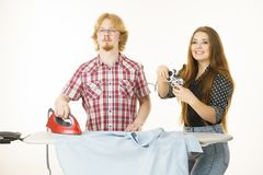 Woman controling man to do ironing. Woman being bossy having fun while steering men using gaming pad. Female controling her boyfriend to do ironing. Household Stock Photos