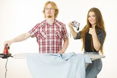 Woman controling man to do ironing. Woman being bossy having fun while steering men using gaming pad. Female controling her boyfriend to do ironing. Household Stock Photo