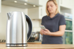 Woman Controlling Smart Kettle Using App On Mobile Phone. Woman Controls Smart Kettle Using App On Mobile Phone stock photography