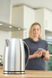 Woman Controlling Smart Kettle Using App On Mobile Phone Royalty Free Stock Photography