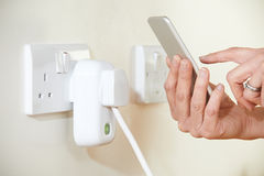 Woman Controlling Smart Plug Using App On Mobile Phone stock images