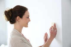 Woman controlling temperature with thermostat Royalty Free Stock Image