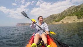 A woman controls the movement of a kayak stock footage