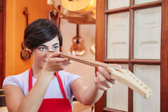 Woman controls quality of fingerboard. Woman controls quality of handmade fingerboard for guitar Stock Image