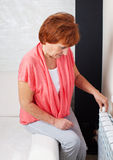 Woman controls the temperature of the radiator Royalty Free Stock Image