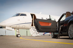 Woman convertable car and corporate private jet Stock Photos