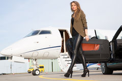 Woman convertable car and corporate private jet Royalty Free Stock Images