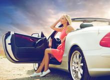 Woman in convertible car over evening sky Royalty Free Stock Photo