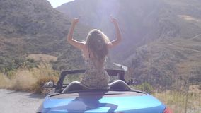 Woman in convertible car. Rear view of relaxing woman with her hands up sitting in blue cabriolet car.Vacation, holiday, journey concept. Slow motion shot of stock video