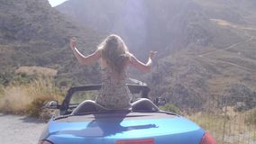 Woman in convertible car. Rear view of relaxing woman with her hands up sitting in blue cabriolet car.Vacation, holiday, journey concept. Slow motion shot of stock footage
