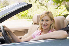 Woman in convertible car smiling Royalty Free Stock Images