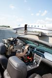 Woman In Convertible With Private Jet At Terminal Stock Images