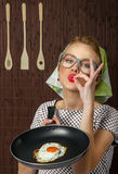 Woman cook. Happy funny woman cook holding pan with fried egg - close up Stock Photos
