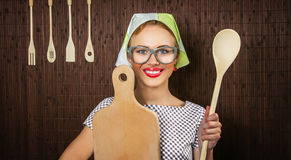 Woman cook. Close-up of a rural funny woman cook with kitchen cutting board and ladle Royalty Free Stock Photos
