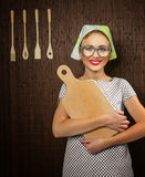 Woman cook. Close-up of a rural funny woman cook with kitchen cutting board Royalty Free Stock Photography