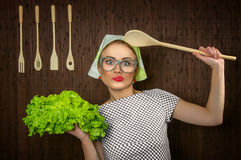 Woman cook. Funny rural woman cook holdin ledle and salad, close-up Royalty Free Stock Images