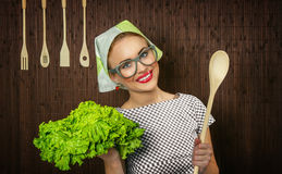Woman cook. Funny rural woman cook holdin ledle and salad, close-up Stock Image