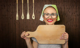 Woman cook. Close-up of a rural funny woman cook with kitchen cutting board Royalty Free Stock Photos