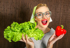 Woman cook. Funny woman cook holding salad and sweet pepper, close up of a housewife Stock Images