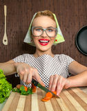 Woman cook. Happy funny woman cook working in the kitchen cutting carrot Royalty Free Stock Images