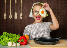 Woman cook. Happy funny woman cook holding pan with fried egg - close up Royalty Free Stock Image