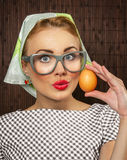 Woman cook. Funny woman cook holding egg,close-up Royalty Free Stock Photo