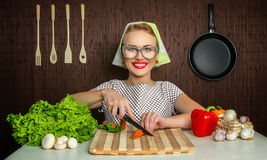 Woman cook. Happy woman cook working in the kitchen cutting carrot Royalty Free Stock Photos