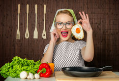 Woman cook. Happy funny woman cook holding pan with fried egg - close up Stock Image