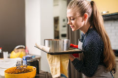Woman cook in apron holds hot pan with fresh cake Royalty Free Stock Photography