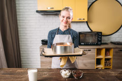 Woman cook in apron holds pan with fresh cake Royalty Free Stock Photo