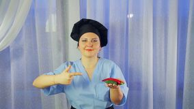 Woman cook in apron smiles, holds chilli peppers in her hand and points to them stock video footage