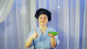 Woman cook in apron smiles, holds cucumbers in her hand and shows the class. stock footage