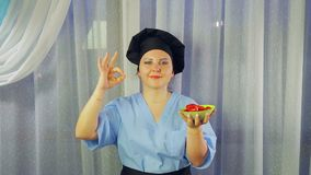 Woman cook in apron smiles, holds green salad in hand and shows hand OK stock video