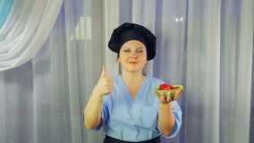 Woman cook in apron smiles, holds in her hand cherry tomatoes in a plate and shows class with her hand stock footage