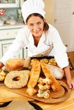 Woman cook with baked goods. Woman cook and table with lot of homemade baked goods Royalty Free Stock Photos