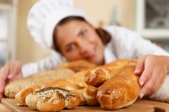 Woman cook with baked goods. Woman cook and table with lot of homemade baked goods Stock Photography