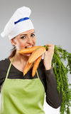 Woman cook biting carrots Royalty Free Stock Photography