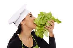Woman cook biting lettuce Stock Photos