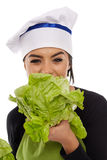 Woman cook biting lettuce Royalty Free Stock Photography