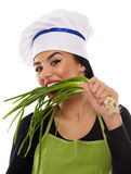 Woman cook biting spring onions Stock Photos
