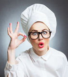 Woman cook, chef. Young woman cook chef gesturing showing ok, isolated over gray wall Royalty Free Stock Images