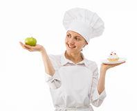 Woman cook chooses between an apple and a cake Royalty Free Stock Photography