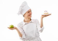 Woman cook chooses between an apple and a cake Royalty Free Stock Image