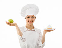 Woman cook chooses between an apple and a cake Stock Images