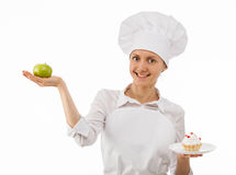 Woman cook chooses between an apple and a cake Stock Photo